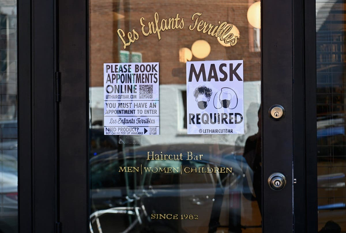 "In this file photo a ""Mask Required"" sign is seen outside 'Les Enfants Terribles' hair salon and barber shop amid the coronavirus pandemic on June 22, 2020 in the Brooklyn Borough of New York City. (AFP)"