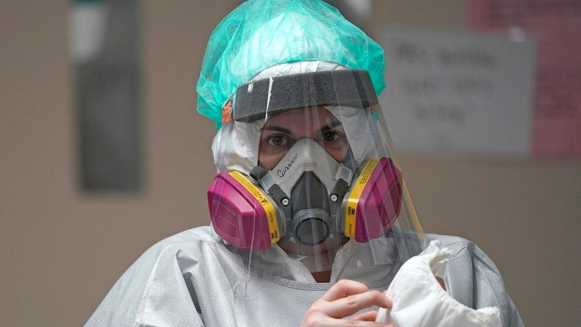 Registered Nurse Candace Trammeor grabs shoe coverings inside the Coronavirus Unit at United Memorial Medical Center, Monday, July 6, 2020, in Houston. (AP)