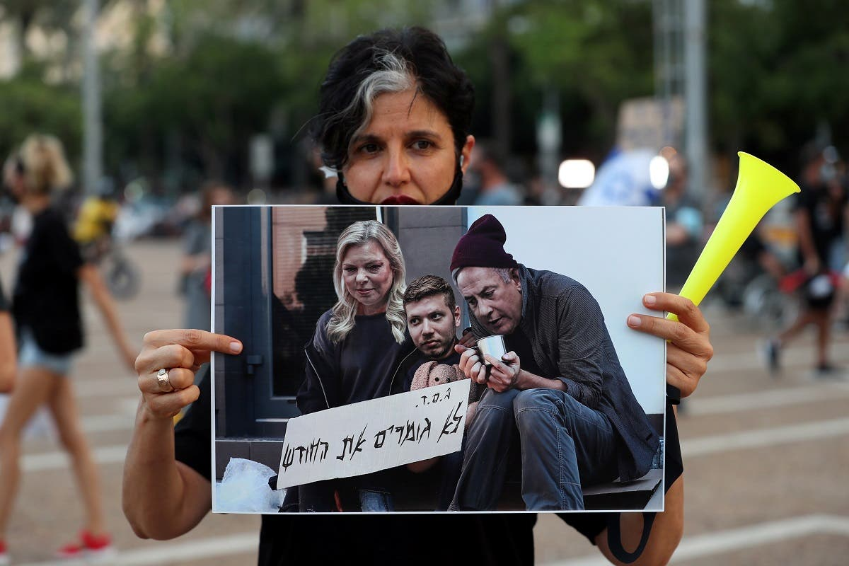 An Israeli woman holds a manipulated photo during a protest against the government's response to the financial fallout of the coronavirus at Rabin square in Tel Aviv, Israel July 11, 2020. (Reuters)