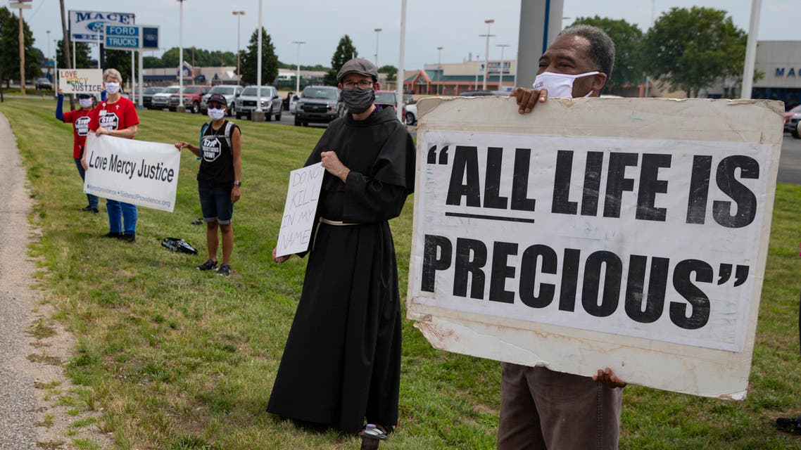 A protester holds a sign demonstrating against the death penalty in the US. (AP)
