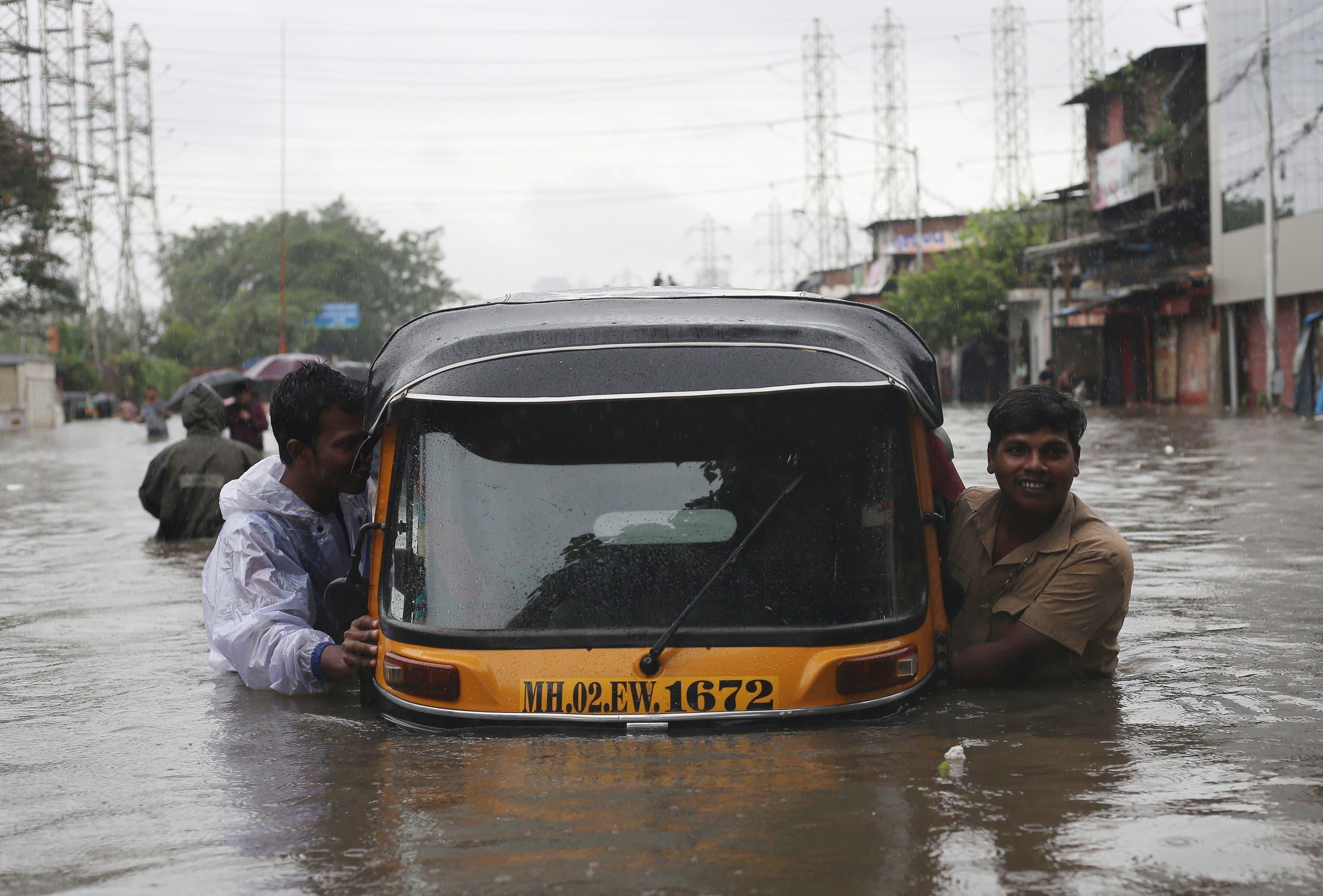 Men push an auto-rickshaw through a flooded road after a heavy rainfall in Mumbai. (Reuters)