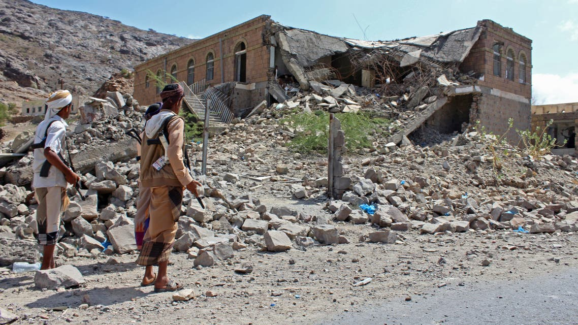 Yemeni fighters loyal to the government backed by the Saudi-led coalition walk past debris along a road near the town of Al-Shurayja in the southern Lahij province, about 66 kilometres southwest of the city of Taez on March 27, 2018.