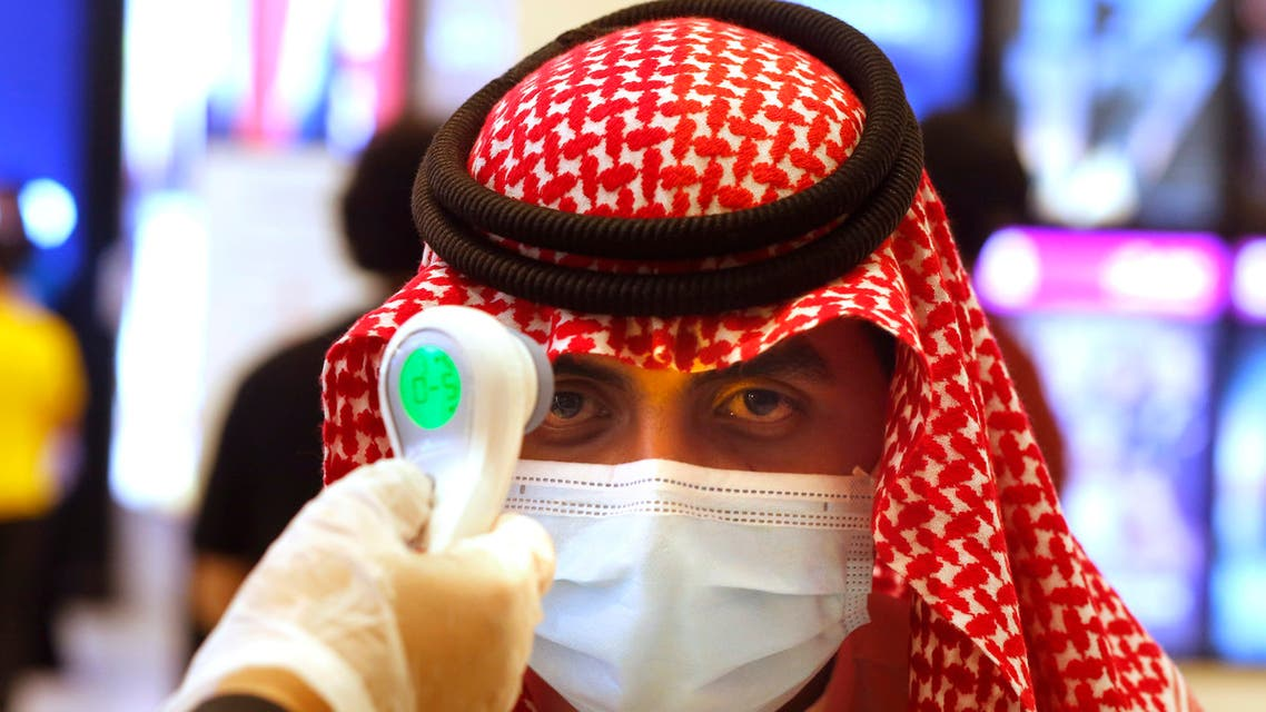 A Saudi cinema viewer has his temperature taken as he wears a face mask to help curb the spread of the coronavirus, at VOX Cinema hall in Jiddah, Saudi Arabia, Friday, June 26, 2020, after the announcement of easing of lockdown measures amid the coronavirus outbreak. (AP Photo/Amr Nabil)