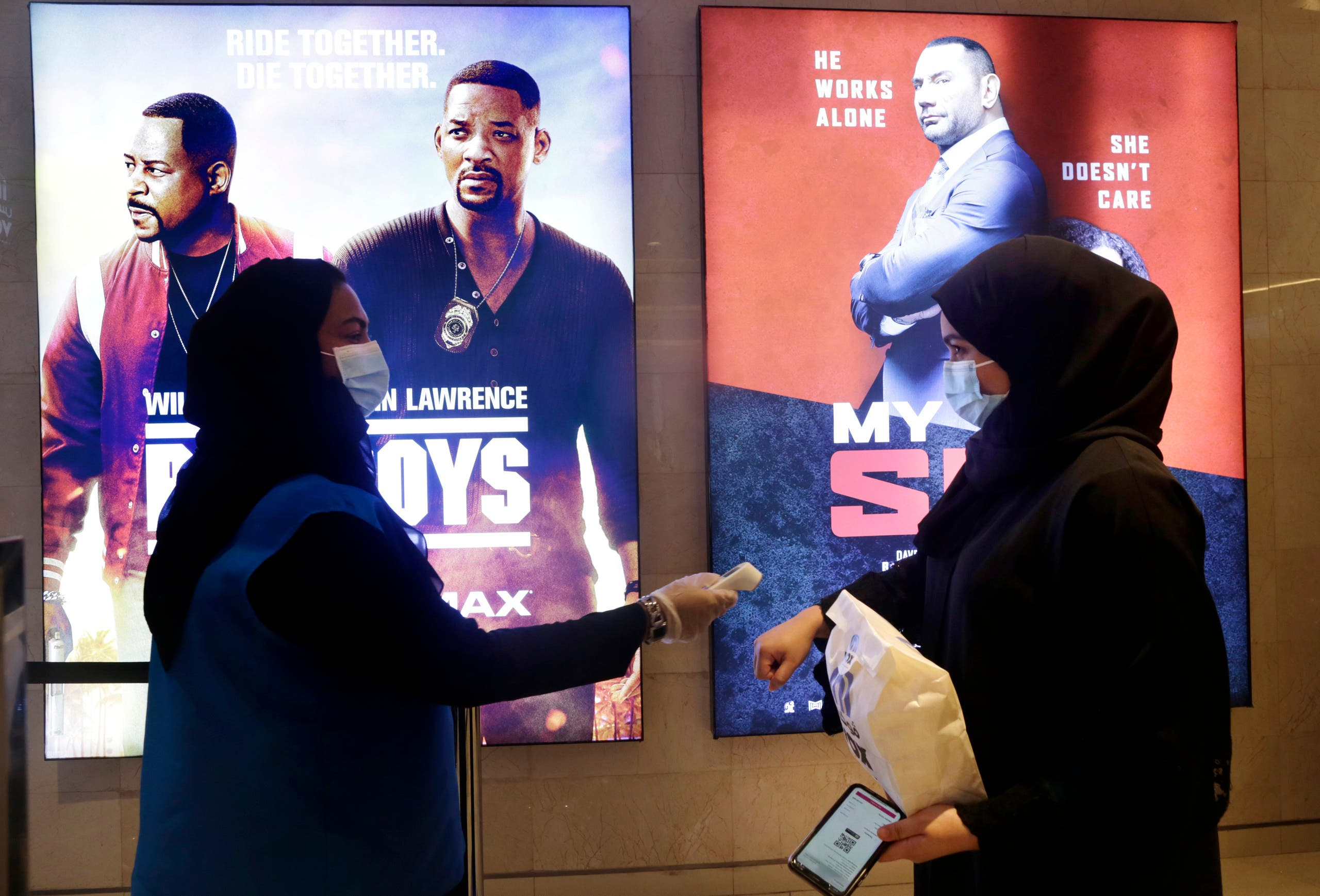 A Saudi movie viewer has her temperature taken as she wears a face mask to help curb the spread of the coronavirus, at VOX Cinema hall in Jiddah, Saudi Arabia, Friday, June 26, 2020, after the announcement of easing of lockdown measures amid the coronavirus outbreak. (AP Photo/Amr Nabil)