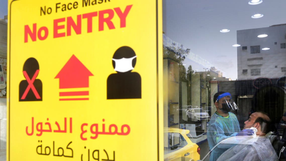 A poster showing healthy procedures to help curb the spread of the coronavirus, hangs at a barber shop window in Jiddah, Saudi Arabia, Sunday, June 28, 2020. (AP Photo/Amr Nabil)
