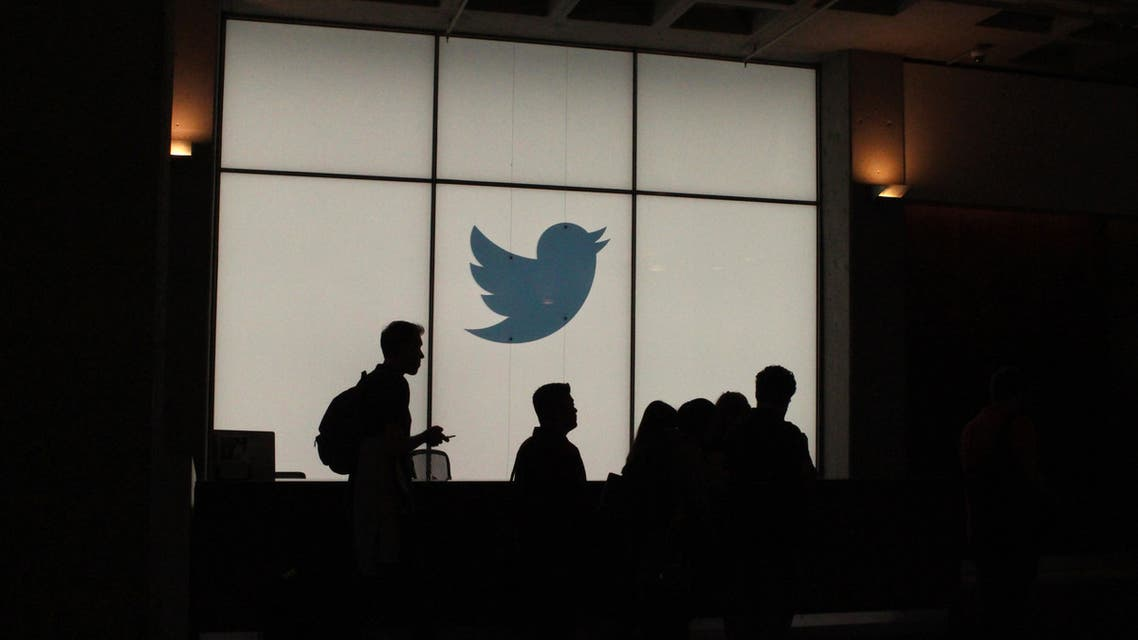 Employees walk past a lighted Twitter log as they leave the company's headquarters in San Francisco on August 13, 2019. (AFP)