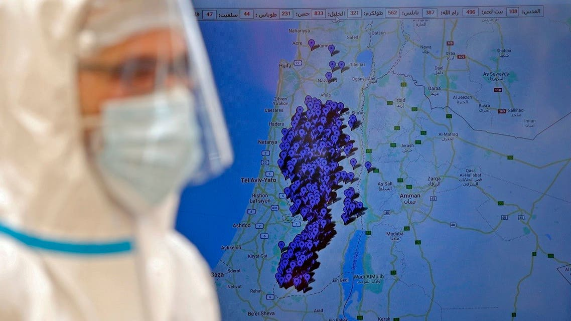 A doctor, from the Palestinian Ministry of Health, stands next to a map tracking the location of people infected with the novel coronavirus COVID-19 in Hebron in the occupied West Bank on July 15, 2020. (AFP)