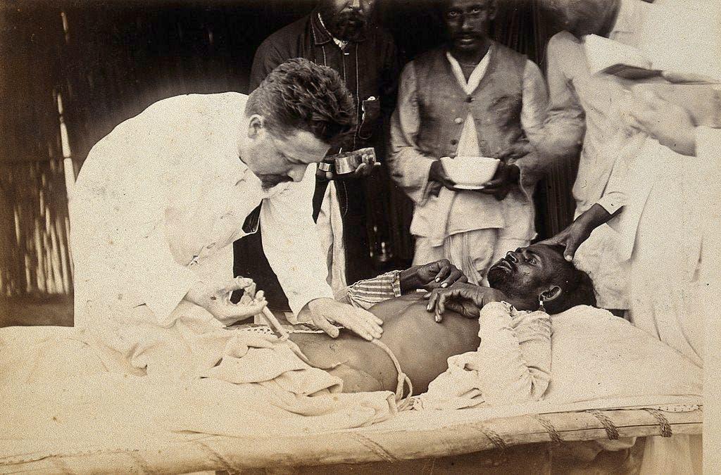 صورة لعملية علاج أحد المصابين بالطاعون بكراتشي عام 1897