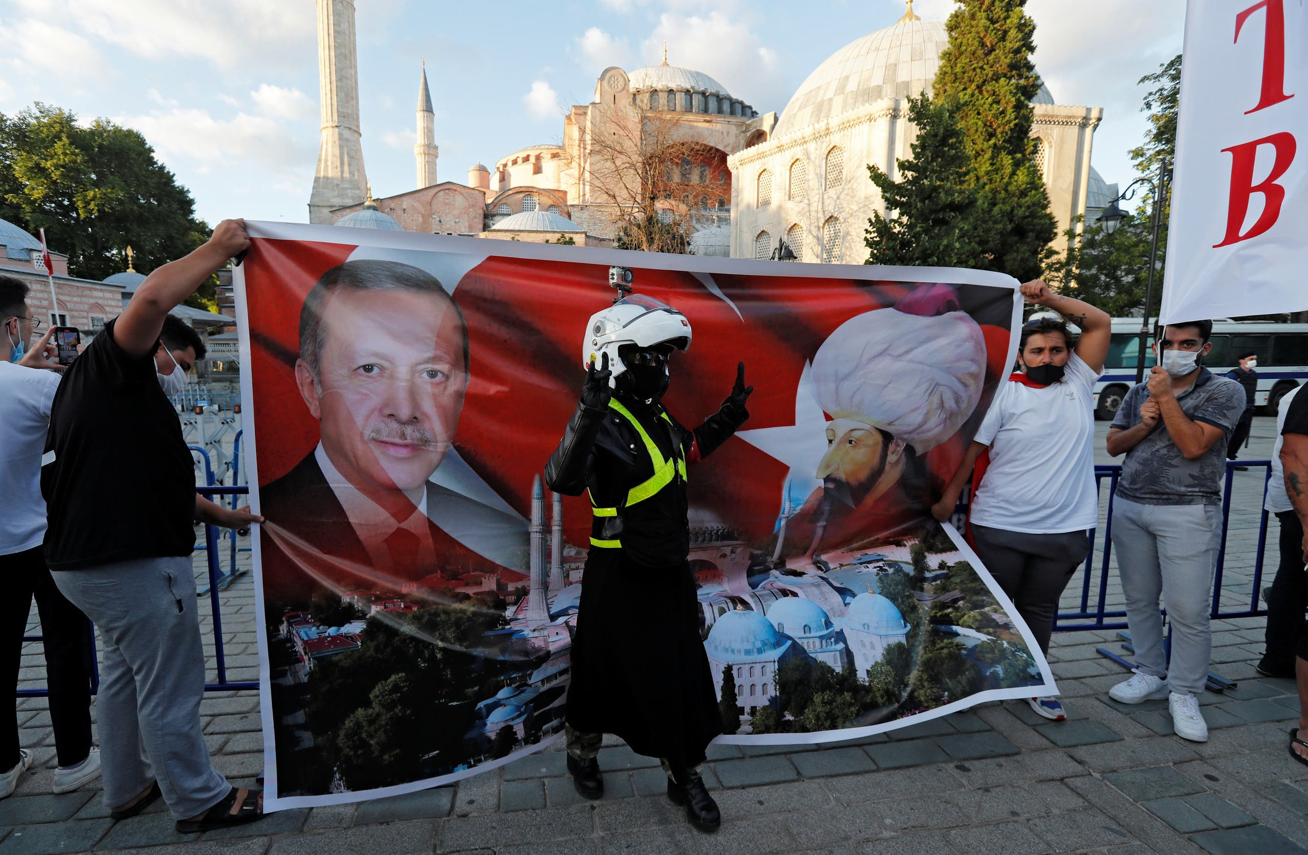 People hold a placard showing Turkish President Tayyip Erdogan and Ottoman sultan Mehmed II in front of the Hagia Sophia or Ayasofya in Istanbul. (Reuters)