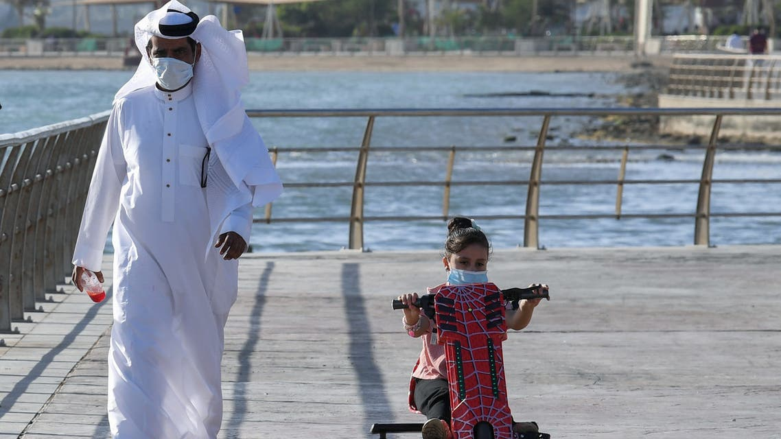 A Saudi man and his daughter stroll down the seafront promenade in the Saudi seaport of jeddah, on June 21, 2020, as the country re-opens following the lifting of a lockdown due to the COVID-19 pandemic.