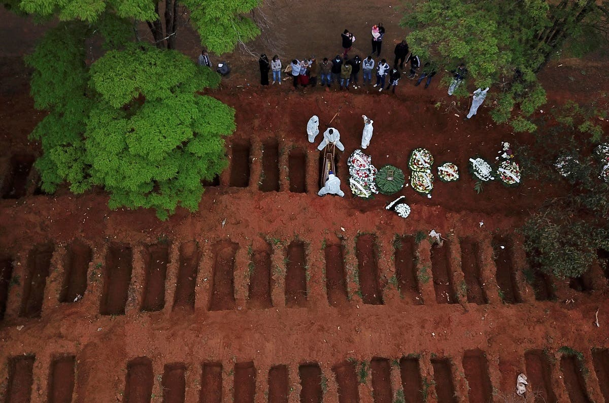 Gravediggers wearing protective suits bury a coffin at Vila Formosa cemetery during the outbreak of the coronavirus disease (COVID-19), in Sao Paulo, Brazil. (Reuters)