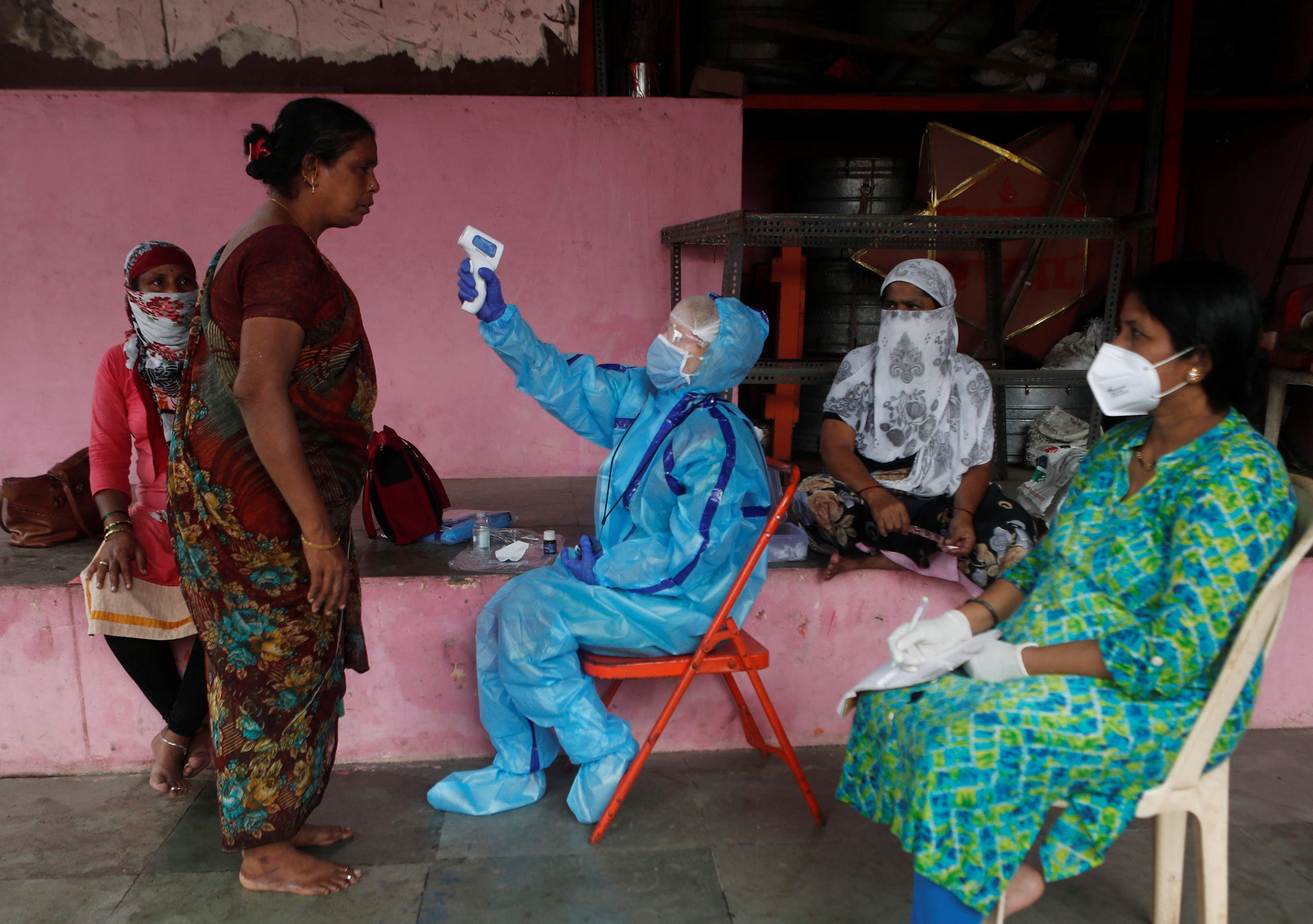 A healthcare worker tests people at a coronavirus center in Mumbai, India. (File photo, Reuters)