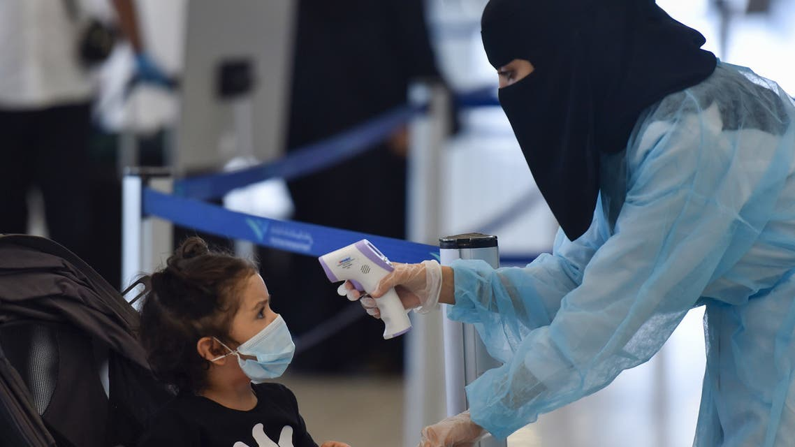 A Saudi health worker takes the temperature of a child at terminal 5 in the King Fahad International Airport, designated for domestic flights, in the capital Riyadh on May 31, 2020, after authorities lifted the ban on flights within the country.