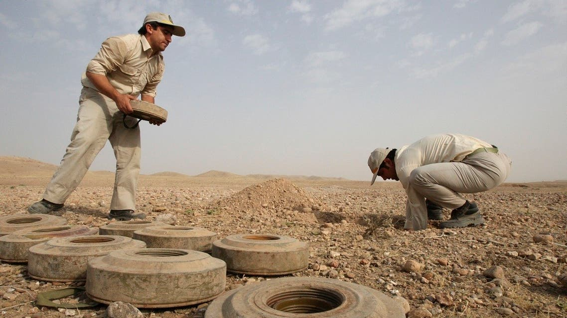 In this picture taken on Sunday, July 24, 2011, Iranian army members Hamzeh Nazeri, left, and Yasser Moazzami Goudarzi, prepare defused landmines to detonate during de-mining operations. (AP)
