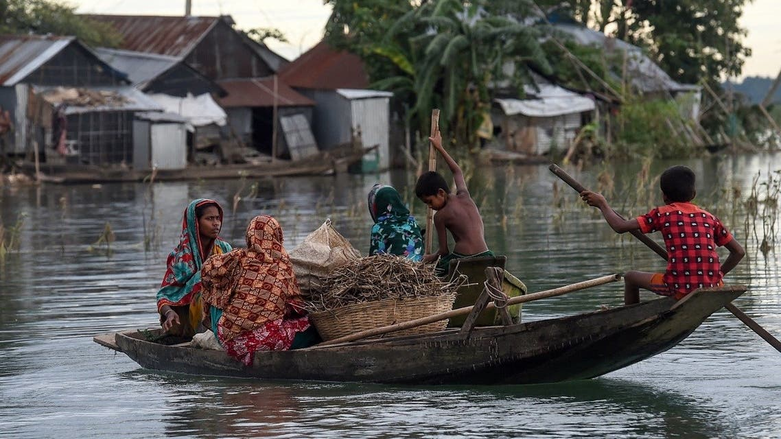 Women and children use a boat to make their way through floodwaters in Sunamganj on July 15, 2020. (AFP)