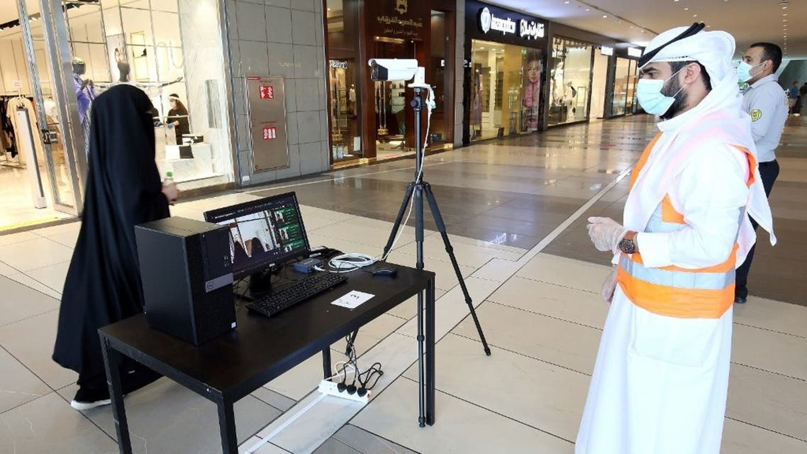Kuwaiti security check a visitor's temperature at the entrance of a mall on June 30, 2020 in Kuwait City. (AFP)