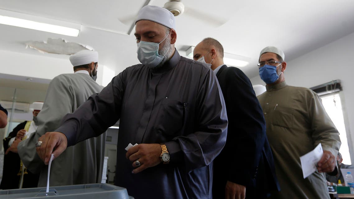 A Syrian cleric casts his ballot at a voting station in the capital Damascus on July 19, 2020. (AFP)