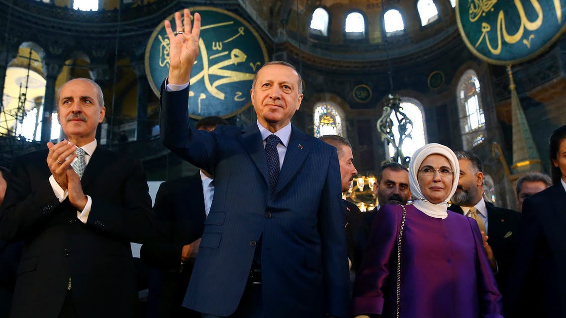 Turkey's President Recep Tayyip Erdogan, center, accompanied by his wife Emine, right, waves to supporters as he walks in the Byzantine-era Hagia Sophia on March 31, 2018. (AP)