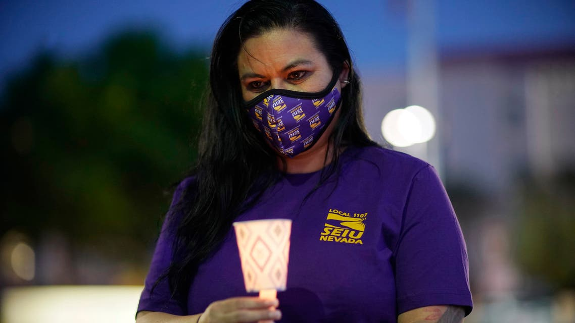 A healthcare worker holds up a candle during a vigil for healthcare workers amidst the coronavirus outbreak at St. Rose Dominican Hospital, Siena Campus, Thursday, April 30, 2020, in Las Vegas. (AP)