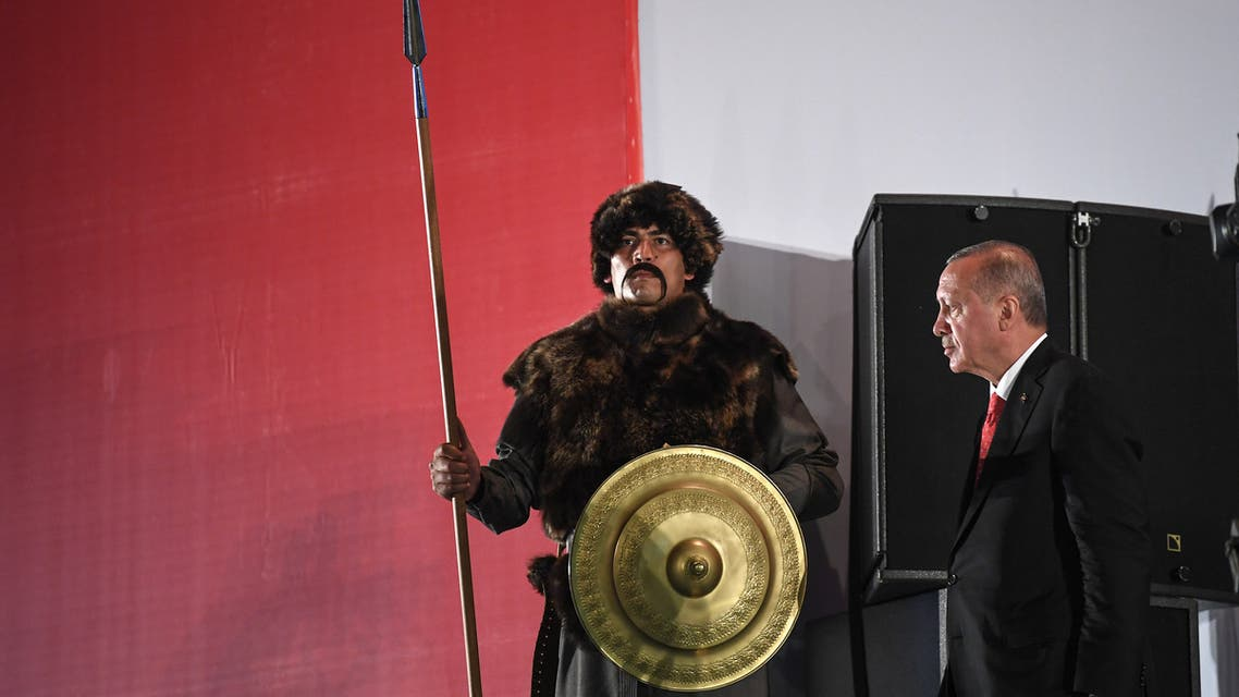 Turkish president Recep Tayyip Erdogan (R) passes next to a Turkish soldier wearing a ottoman uniform during a third anniversary commemoration rally in Istanbul on July 15, 2019. (AFP)