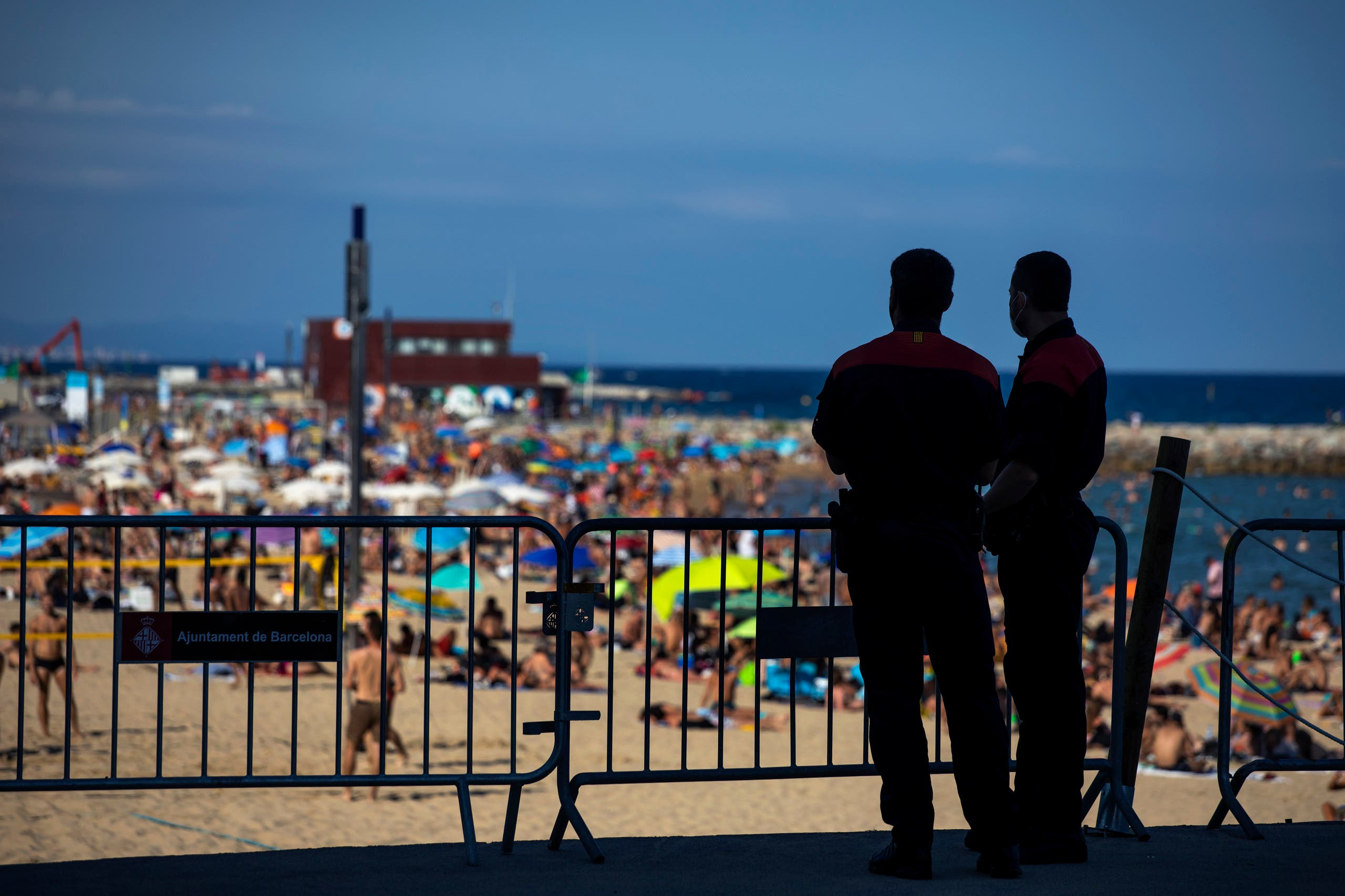 Police officers guard a barrier to stop people entering the beach, in Barcelona on July 18, 2020. (AP)