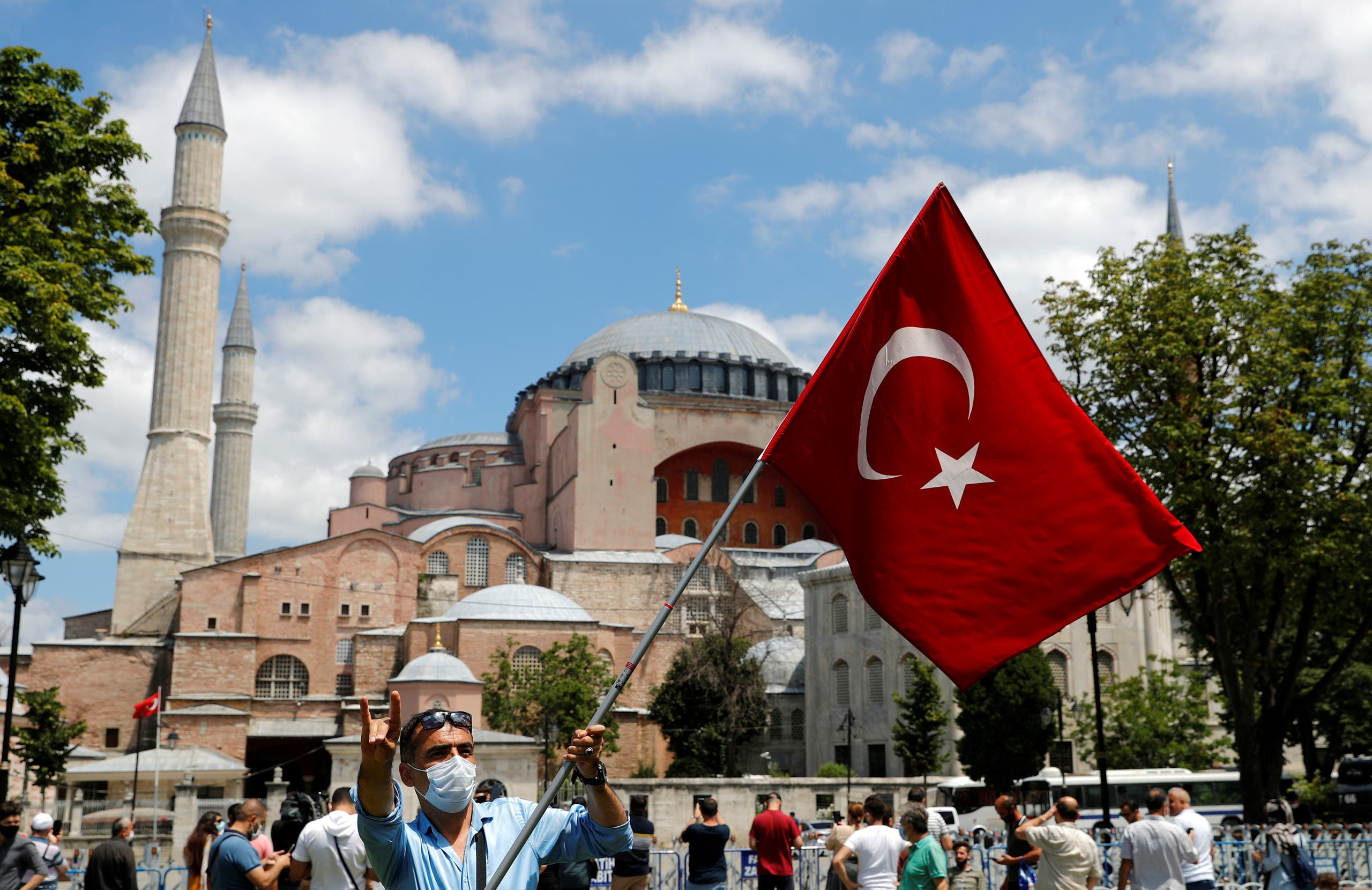 A man waves a Turkish flag as he makes the nationalist grey wolf sign in front of the Hagia Sophia in Istanbul on July 17, 2020. (Reuters)
