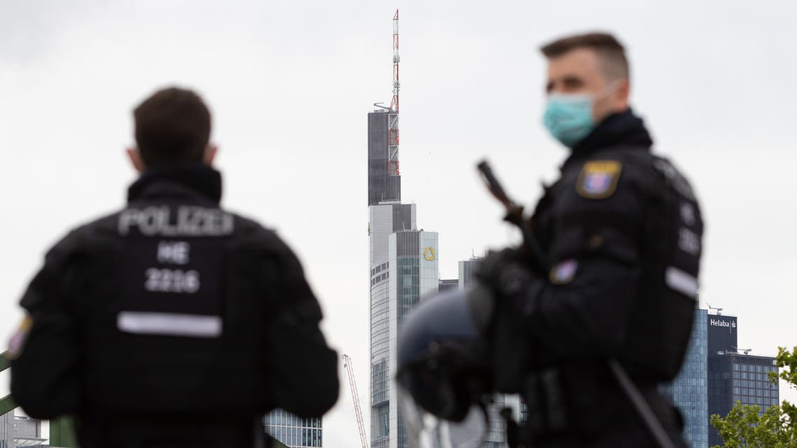 n this file photo taken on May 23, 2020 police officers wearing face masks are pictured in during a rally against restrictions in place to limit the spread of the new coronavirus COVID-19 pandemic in Frankfurt. (AFP)