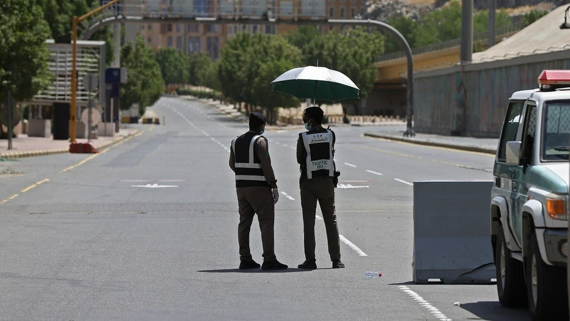 Police officers man a checkpoint in a street in Saudi Arabia's holy city of Mecca on April 3, 2020. (AFP)
