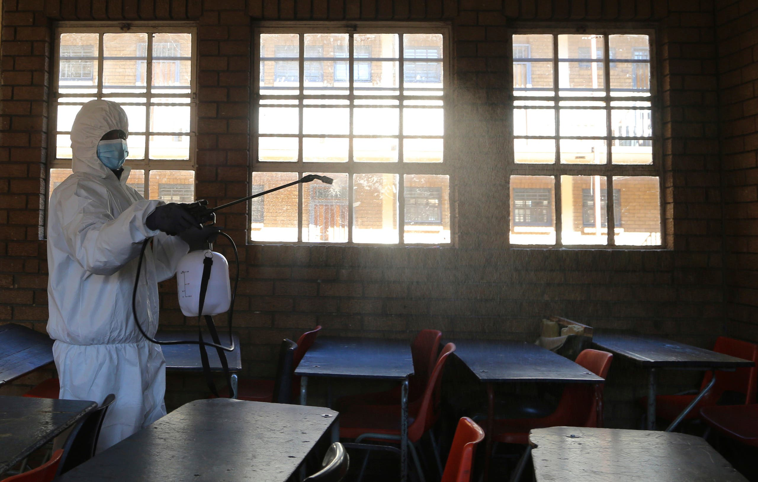 In this May 26, 2020, a worker from Bidvest Prestige wearing personal protective equipment, sprays disinfectant in a classroom to help reduce the spread the coronavirus ahead of the reopening of Landulwazi Comprehensive School, east of Johannesburg, South Africa. (AP)