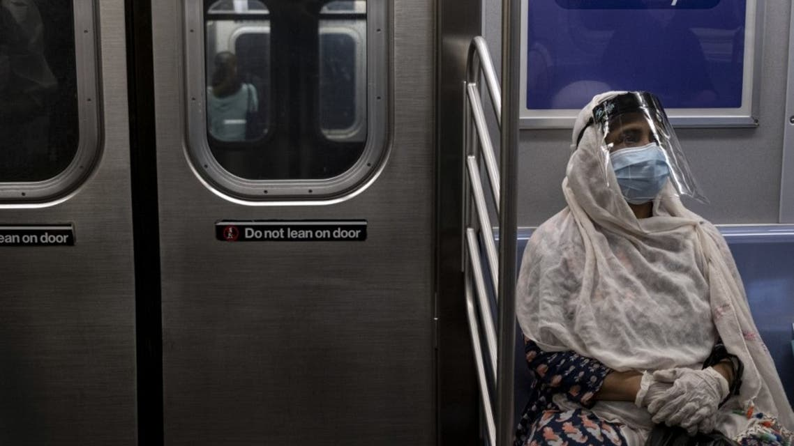A woman wearing a face mask and shield sits in a subway train during rush hour amid the coronavirus pandemic on July 16, 2020, in New York City. (AFP)