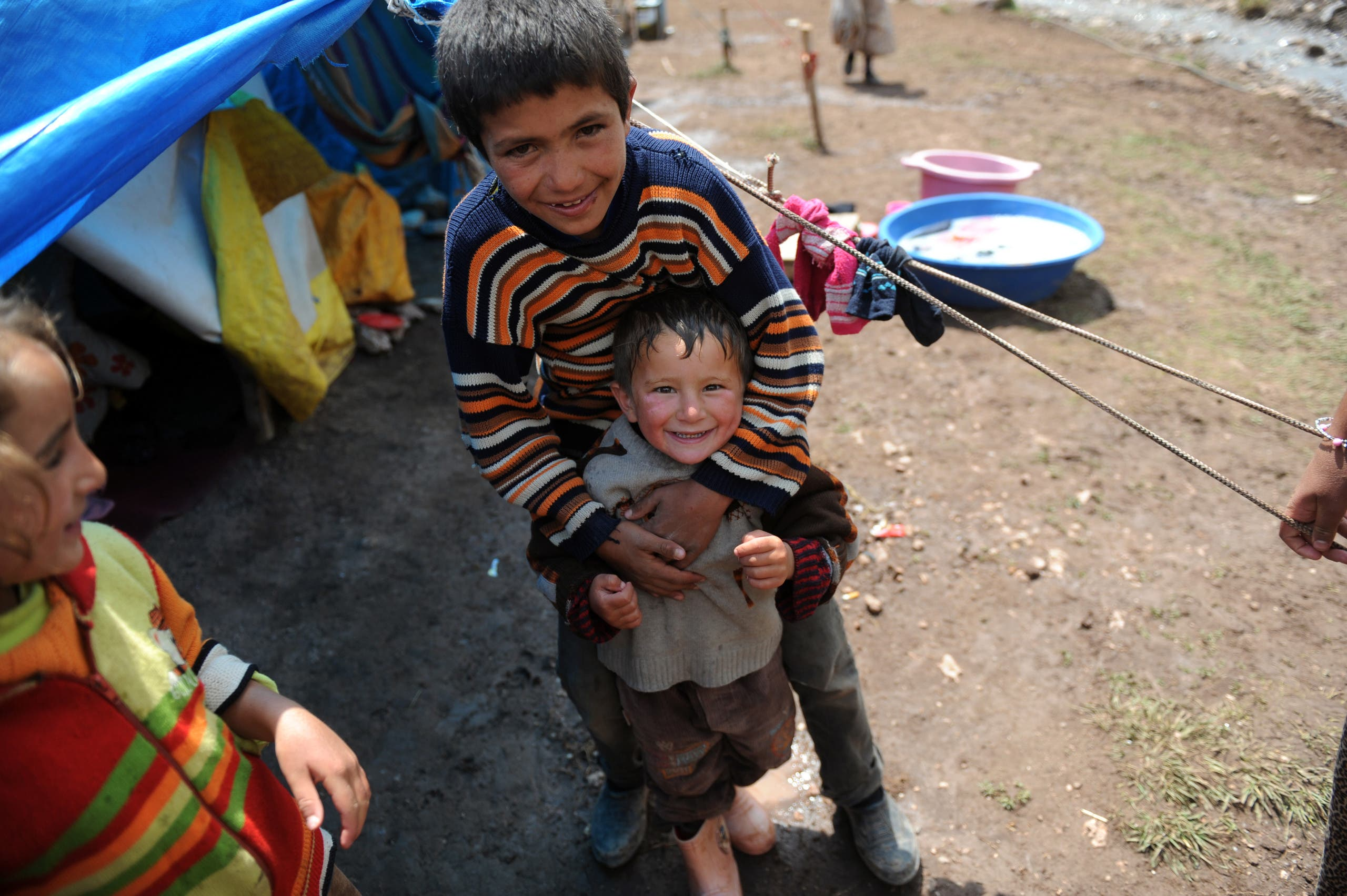 Kurdish children smile for the camera in Gurpinar district near Van on June 26, 2012. (AFP)