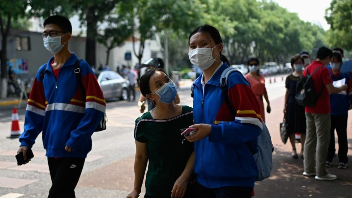 A mask-clad student arrives with a family member before entering her school in Beijing on July 8, 2020. (AFP)