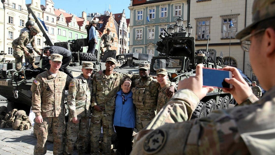 A file photo shows a woman takes a picture with U.S. soldiers, who are part of a NATO multinational battalion battlegroup on their way from Germany to Orzysz, northeastern Poland. (Reuters)
