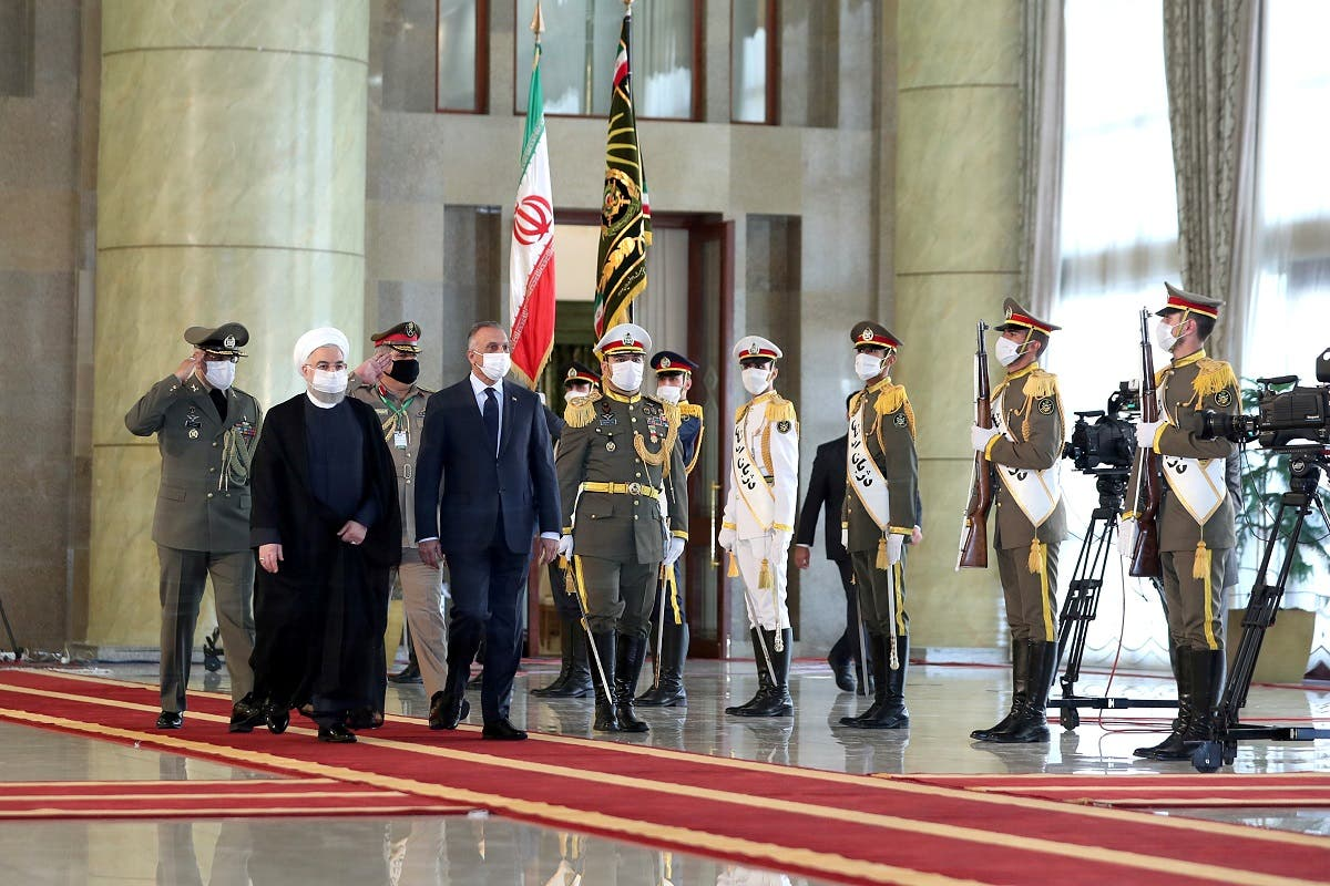 Iranian President Rouhani and Iraqi PM al-Kadhimi walk during a welcome ceremony, as they wear protective masks, in Tehran, Iran, July 21 2020. (Reuters)