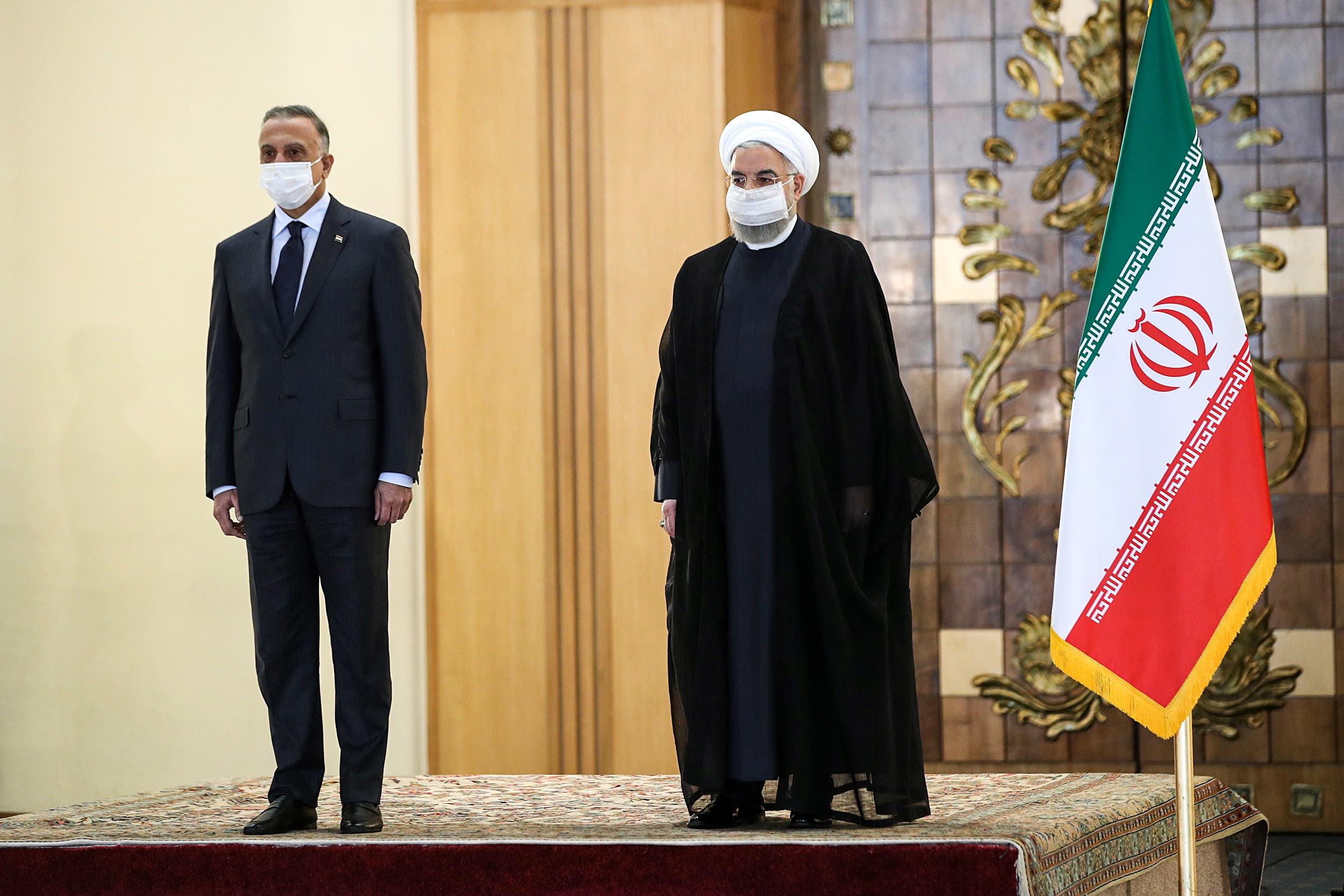 A handout picture provided by the Iranian presidency on July 21, 2020, shows the mask-clad President Hassan Rouhani (R) receiving Iraq's Prime Minister Mustafa al-Kadhimi (L) in the capital Tehran.