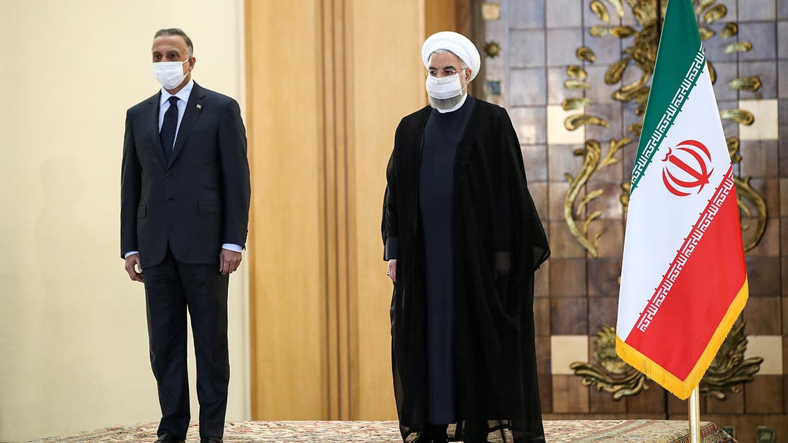 A handout picture provided by the Iranian presidency on July 21, 2020, shows the mask-clad (COVID-19 coronavirus pandemic precaution) President Hassan Rouhani (R) receiving Iraq's Prime Minister Mustafa al-Kadhemi (L) in the capital Tehran.