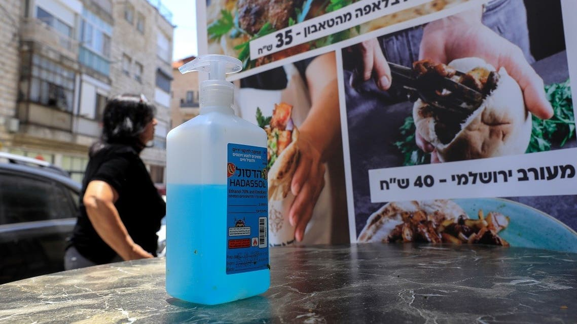 A bottle of sanitizing gel stands at the entrance of restaurant in Jerusalem on May 27, 2020. (AFP)