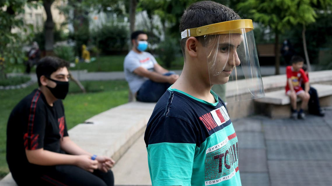 A boy wearing a face shield watches kids playing, following the outbreak of the coronavirus disease (COVID-19), in Tehran, Iran, July 8, 2020. WANA (West Asia News Agency) Abdollah Heidari via REUTERS ATTENTION EDITORS - THIS PICTURE WAS PROVIDED BY A THIRD PARTY
