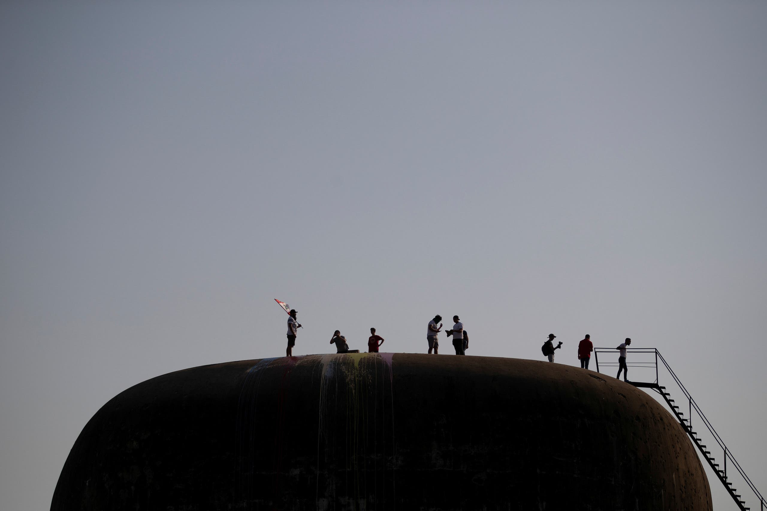 Demonstrators stand on the rooftop of the Egg, an abandoned cinema building in Beirut, Lebanon, October 22, 2019. (Reuters)