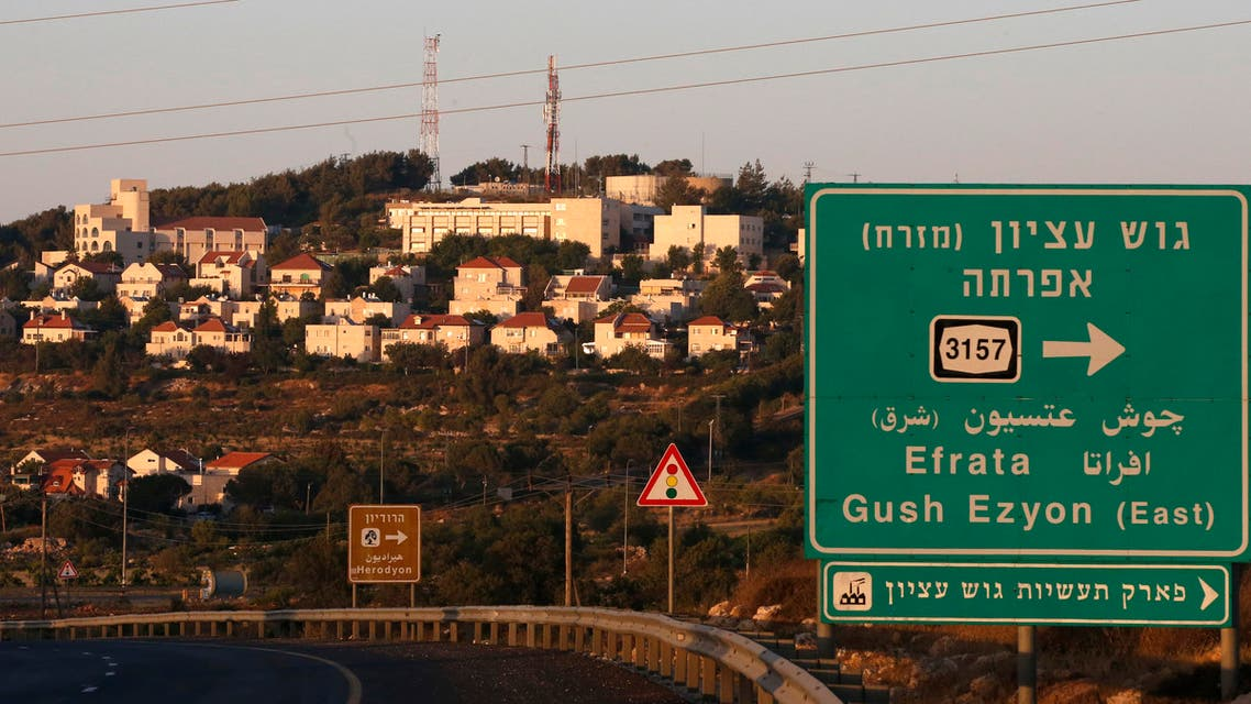 om tThe Israeli settlement of Efrata on the southern outskirts of Bethlehem, behind a road sign towards the right locating the settlement block of Gush Etzion, in the occupied West Bank, on June 27, 2020. (AFP)