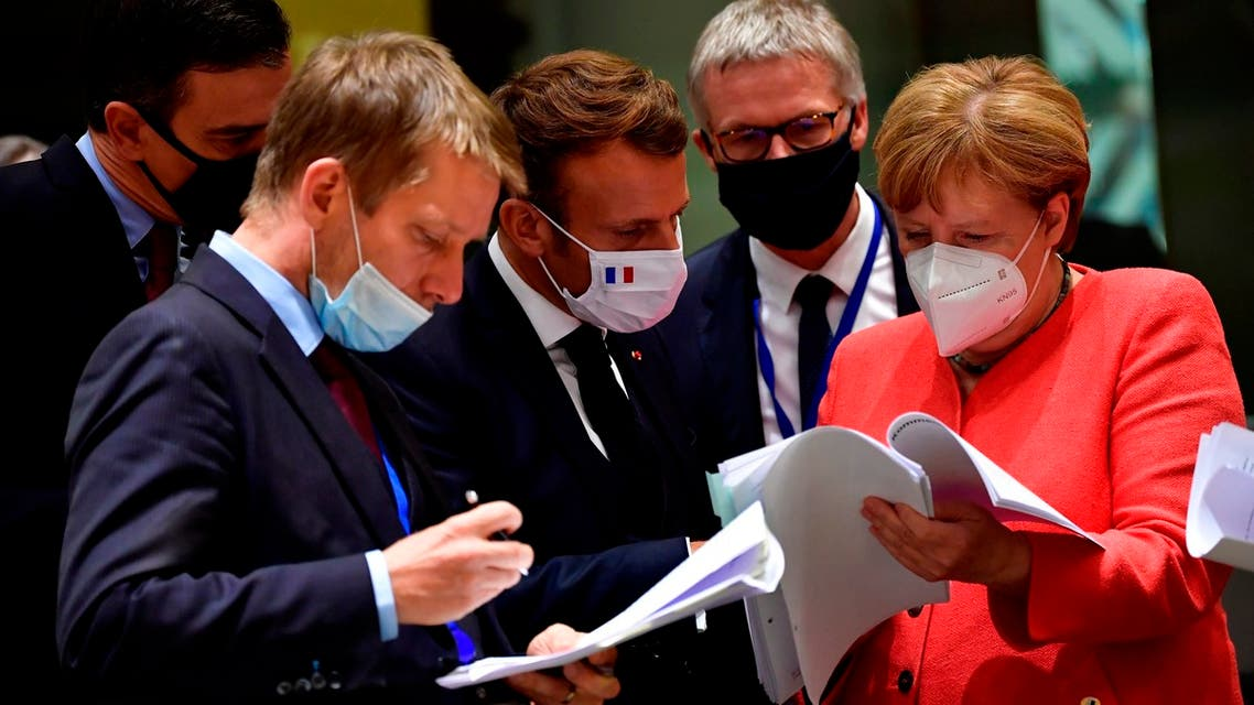 German Chancellor Angela Merkel, right, speaks with French President Emmanuel Macron, center, during a round table meeting at an EU summit in Brussels, July 20, 2020. (AP)
