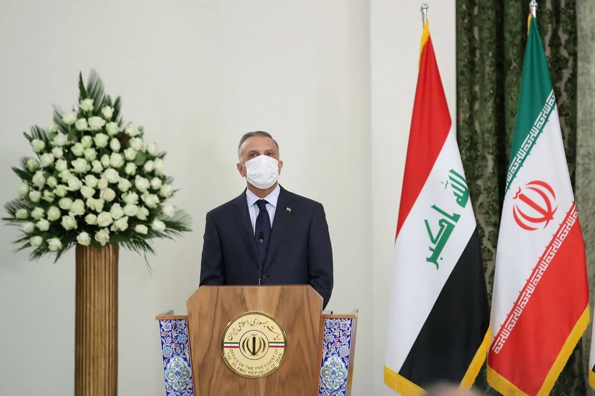 Iraqi Prime Minister Mustafa al-Kadhimi attends a news conference with Iranian President Hassan Rouhani as he wears a protective mask, in Tehran. (Reuters)