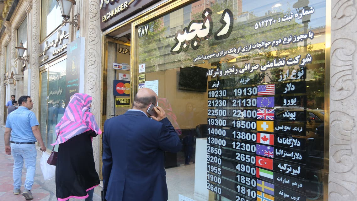 Iranians wait outside a money exchange office in Tehran amid the ongoing COVID-19 pandemic, on June 22, 2020.