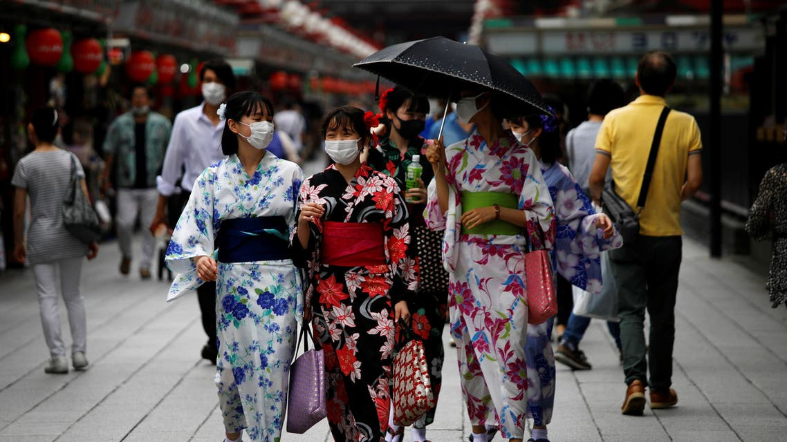 Women in yukata, or casual summer kimonos, wearing protective face masks, walk at Asakusa district amid the coronavirus disease (COVID-19) outbreak in Tokyo. (Reuters)