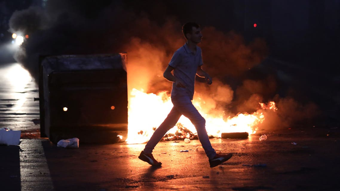 A man walks past burning fire set by demonstrators during a protest over deteriorating living conditions and after the Lebanese government raised subsidised bread prices, in Beirut, Lebanon June 30, 2020. REUTERS/Mohamed Azakir