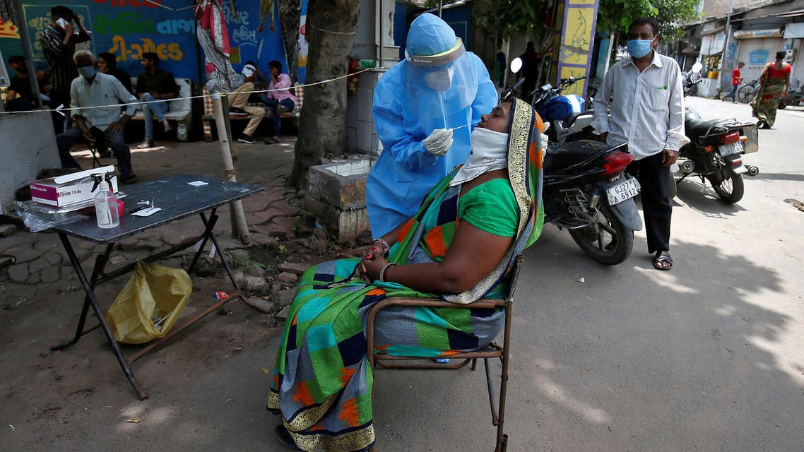 FILE PHOTO: A healthcare worker wearing a protective gear takes a swab from a woman for a rapid antigen test, amidst the coronavirus disease (COVID-19) outbreak, at a roadside testing centre in Ahmedabad, India, July 20, 2020. REUTERS/Amit Dave/File Photo