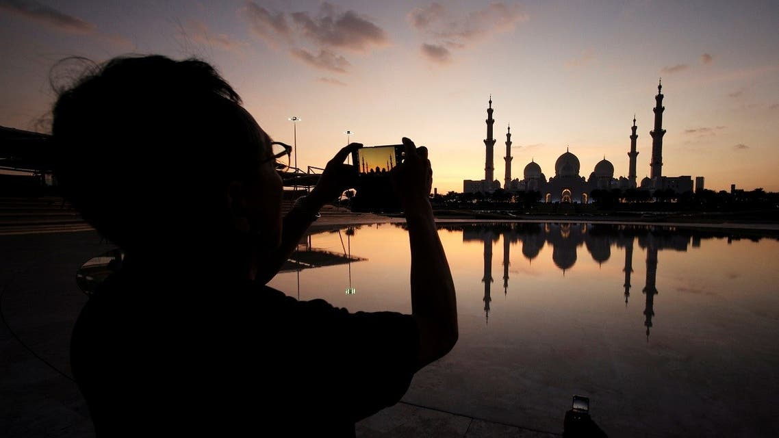 A visitor takes photos of Sheikh Zayed Mosque with their smart phone in Abu Dhabi. (Reuters)
