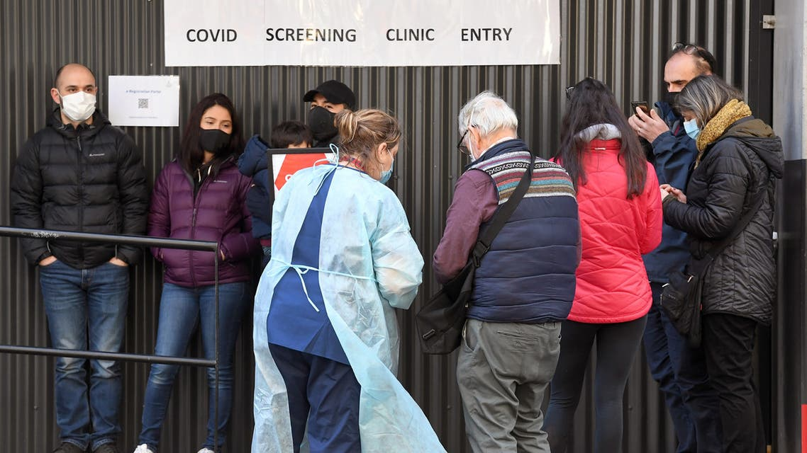 A medical worker (centre L) speaks to people queueing outside a COVID-19 coronavirus testing venue at The Royal Melbourne Hospital in Melbourne on July 16, 2020. Melbourne, which is undergoing a six week lockdown, has recorded 317 new coronavirus cases, the largest biggest daily increase since the pandemic started in Australia.