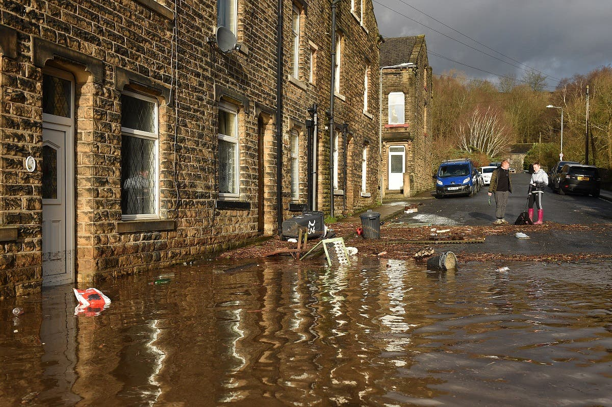 People stand near debris caused by flooding in a street in Mytholmroyd, northern England, on February 9, 2020, after the River Calder burst its banks as Storm Ciara swept over the country. (AFP)