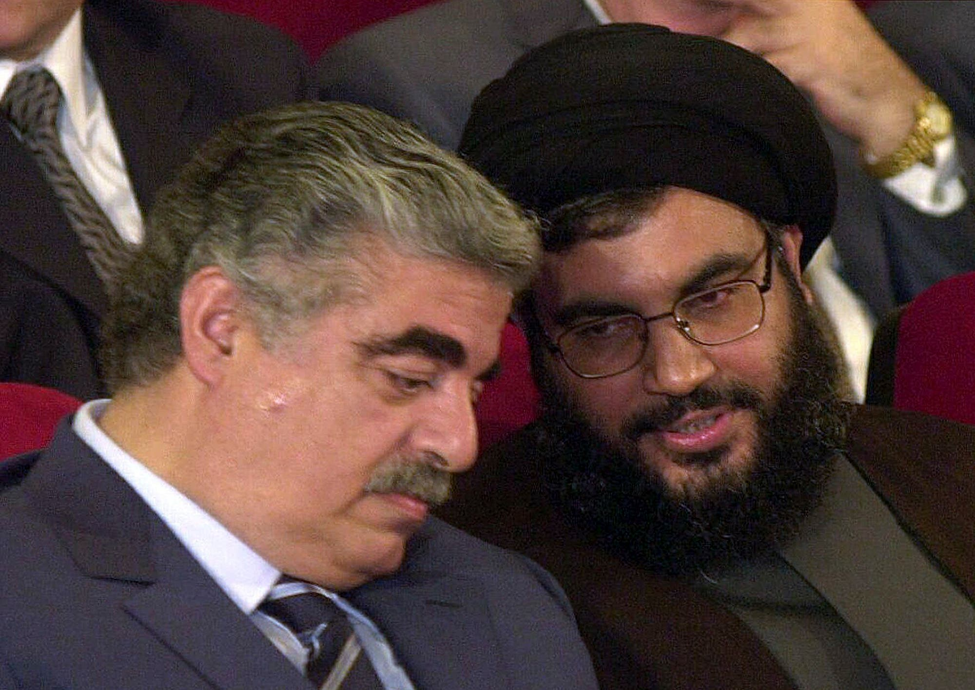 The late Lebanese Prime Minister Rafik Hariri, left, talks with Hezbollah leader Hassan Nasrallah, right, during an official ceremony on May 25, 2001 in Beirut. (File photo: AP)